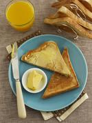 Toast triangles with butter and orange juice - stock photo