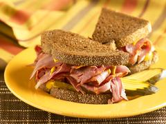Stock Photo of Corned Beef Sandwich with Mustard and Pickles on Pumpernickel Bread; Halved on a