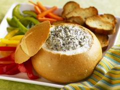 Spinach Dip in a Bread Bowl with Sliced Veggies and Toasted Bread Slices for - stock photo