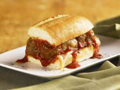 Meatball Sub with Marinara Sauce Dripping Down the Sides; On a White Plate Stock Photos