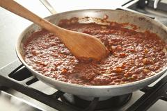 Stirring Pureed Tomatoes into Cooked Vegetables to Make a Chili - stock photo