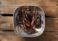 Dried Red Peppers in a Pewter Bowl on Wood Stock Photos