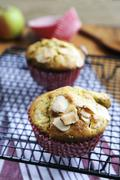 Apple muffins with poppy seeds and almonds on a wire rack - stock photo