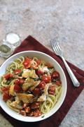 Spaghetti with haddock, tomatoes and capers (seen from above) - stock photo