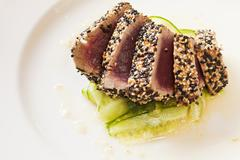 Sesame Encrusted Seared Ahi Tuna in a Spicy Cucumber and Lime Vinaigrette - stock photo