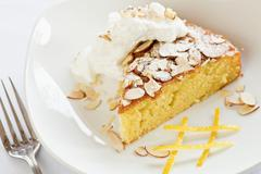 Citrus Olive Oil Cake Topped with Almonds and Whipped Cream - stock photo