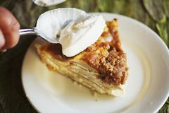 Spooning Whipped Cream onto a Slice of Sour Cream Apple Pie - stock photo