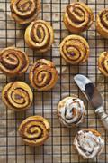 Cinnamon Buns on a Cooling Rack with Vanilla Icing - stock photo