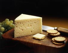 Baby Swiss Cheese Wedge on a Cutting Board with Crackers and Green Grapes - stock photo