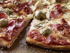 Thin Crust Pizza with Prosciutto and Green Olives Stock Photos