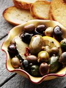 Bowl of Marinated Olives with Slices of Toasted Bread - stock photo
