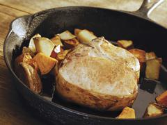 Pork Chop and Potatoes in a Cast Iron Skillet Stock Photos