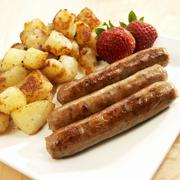 Three Breakfast Sausages with Homefries and Strawberries - stock photo