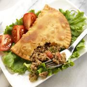 Fried Empanada Broken Open with a Fork; Meat Filling Spilling Out - stock photo