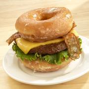 Unhealty Food Bacon Cheeseburger Served on Two Krispie Kreme Donuts Stock Photos
