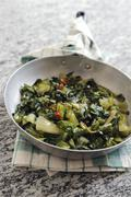 Fried chicory greens with chilli and garlic Stock Photos