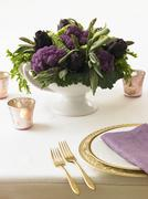 Table Centerpiece Made from Purple Artichokes and Cauliflower - stock photo