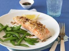 Salmon Fillet with Walnut Crust and Fresh Pea Pods Stock Photos