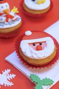 Cupcake with Father Christmas decoration - stock photo