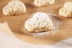 Dusting heart-shaped biscuits with icing sugar Stock Photos