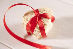 A heart-shaped biscuit tied with a red ribbon - stock photo