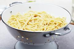 Cooked Spaghetti in a White Metal Strainer Stock Photos