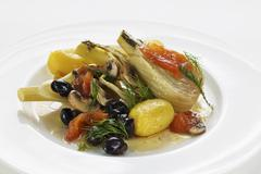 Fennel wrapped in foil cooked with olives, tomatoes and potatoes - stock photo