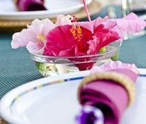A place setting and a bowl of water hibiscus flowers - stock photo