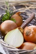 A basket of onions, whole and halved - stock photo