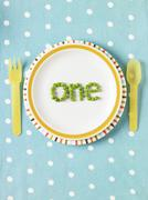 "The word ""one"" spelled out with peas on a plate - stock photo"