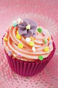 A cupcake decorated with buttercream, sugar sprinkles and a sugar flower Stock Photos