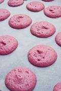 Piles of pink macaroon dough on baking paper - stock photo