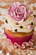 A cupcake decorated with a pink sugar rose and buttercream - stock photo