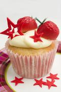 A cupcake decorated with marzipan strawberries and red stars Stock Photos