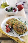 Pan-fried chickpea cakes spiced with cumin and coriander with fresh tomato salsa Stock Photos
