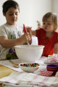 Young boy and girl mixing ingredients in a bowl Stock Photos