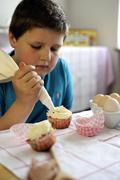 Young boy icing cupcakes - stock photo