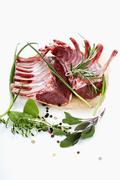 Raw lamb chops with various herbs and spices - stock photo