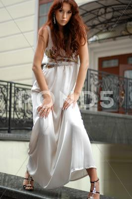 Stock photo of woman in long dress near a hotel