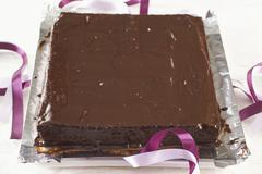 A square chocolate cake on a piece of silver foil Stock Photos