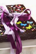 Chocolate cake decorated with sugar flowers, butterflies and a gift ribbon Stock Photos