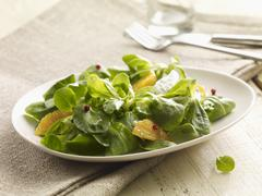 Lamb's leaf lettuce with orange wedges Stock Photos