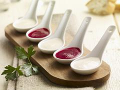 Kohlrabi and beetroot sauce on porcelain spoons - stock photo