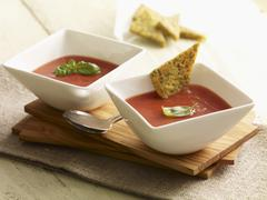 Cream of tomato soup with herb and polenta triangles - stock photo