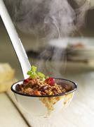 Steaming chilli con carne in a ladle - stock photo