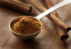 Ground Cinnamon in a Measuring Spoon; Cinnamon Sticks Stock Photos