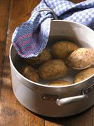Potatoes in a pot of water Stock Photos