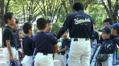 A coach is teaching kids at baseball practice in Japan Stock Footage