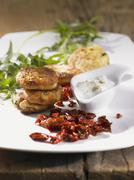 Vegetable fritters with a dip and dried tomatoes Stock Photos
