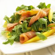Arugula Salad with Salmon and Mango on a White Plate Stock Photos